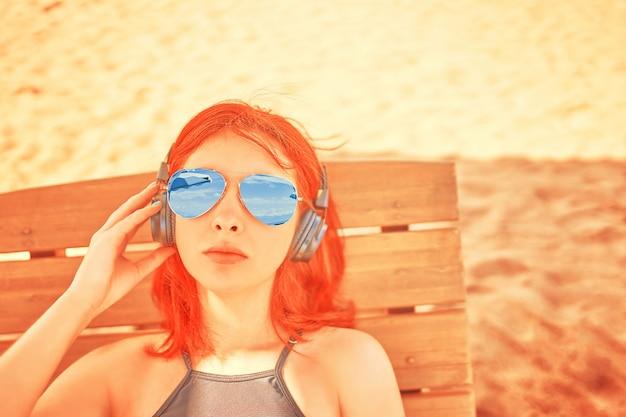 Mooie vrouw die in zonnebril aan muziek op het strand luistert.