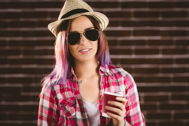 Mooie vrouw die in zonnebril koffiekop houdt