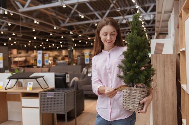 Mooie vrouw die ingemaakte kerstboom onderzoekt, die bij meubilairopslag winkelt