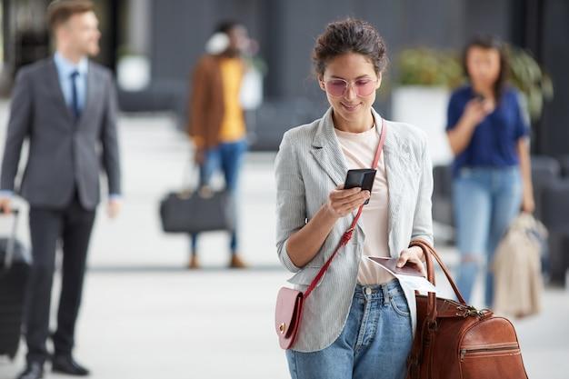 Mooie vrouw die internet in luchthaven gebruiken