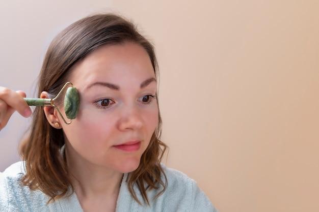 Mooie vrouw die jade gezichtsroller vasthoudt en gezichtsmassages maakt thuis huidverzorgingsconcept