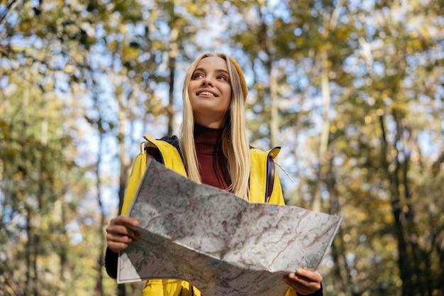 Mooie vrouw die kaart gebruikt om in de herfstbos te navigeren. reis concept