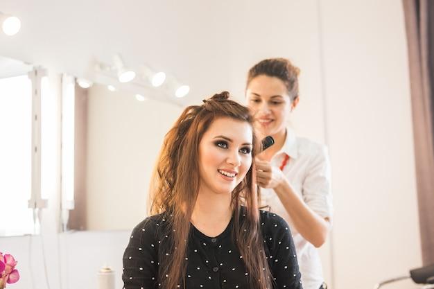Mooie vrouw die kapsel krijgt door kapper in de schoonheidssalon