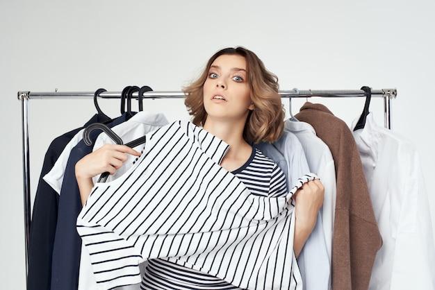 Mooie vrouw die kleren geïsoleerde achtergrond probeert. hoge kwaliteit foto