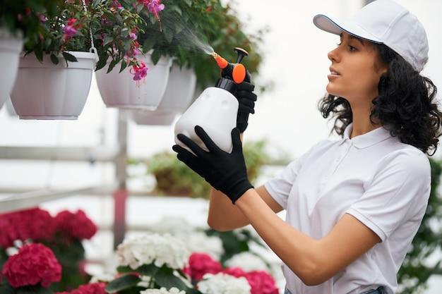 Mooie vrouw die kleurrijke bloemen besproeit met water
