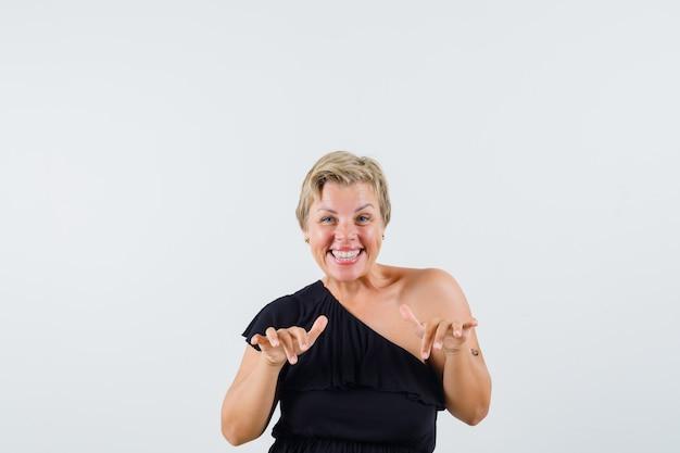 Mooie vrouw die konijntjesgebaar in zwarte blouse toont en geamuseerd kijkt