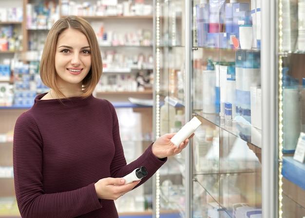 Mooie vrouw die kosmetische flessen in apotheek houdt.