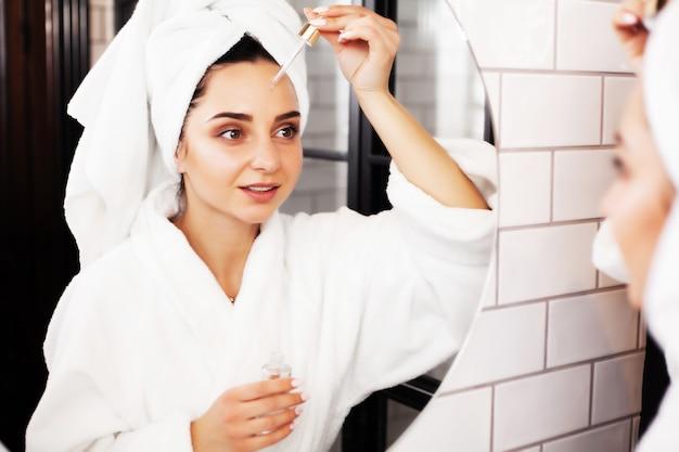 Mooie vrouw die kosmetische procedures doet om voor gezichtshuid in badkamers te zorgen