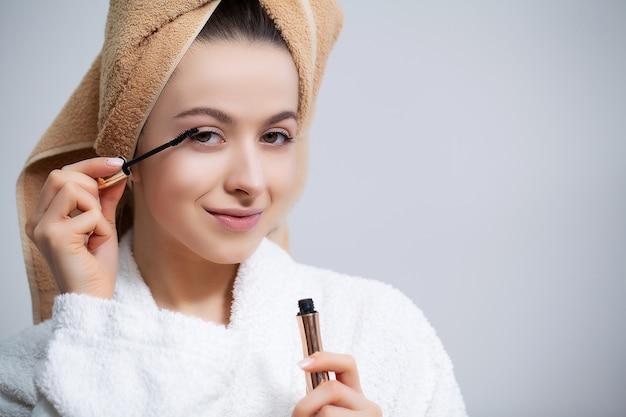 Mooie vrouw die kosmetische procedures thuis voor spiegel doen