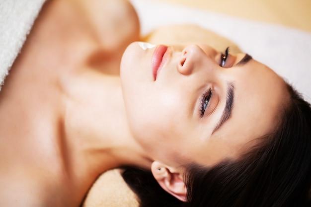 Mooie vrouw die kuuroordbehandelingen krijgt op schoonheidscentrum