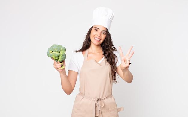 Mooie vrouw die lacht en er vriendelijk uitziet, met nummer drie die een schort draagt en een broccoli vasthoudt