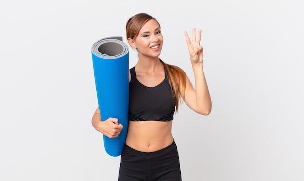 Mooie vrouw die lacht en er vriendelijk uitziet, met nummer drie. yoga concept