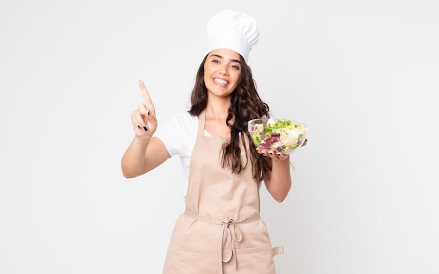 Mooie vrouw die lacht en er vriendelijk uitziet, met nummer één die een schort draagt en een salade vasthoudt