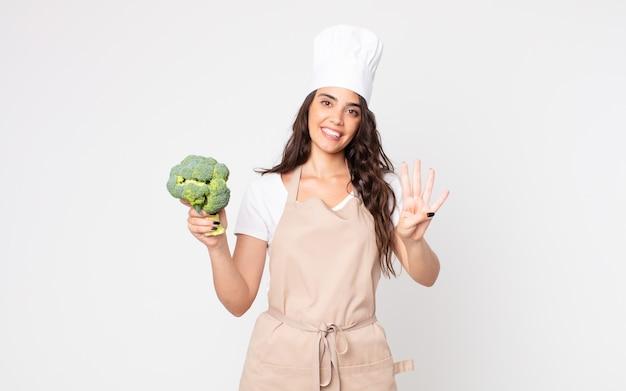 Mooie vrouw die lacht en er vriendelijk uitziet, met nummer vier die een schort draagt en een broccoli vasthoudt