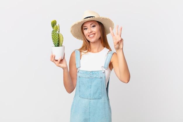 Mooie vrouw die lacht en er vriendelijk uitziet, nummer drie toont en een decoratieve cactusplant vasthoudt