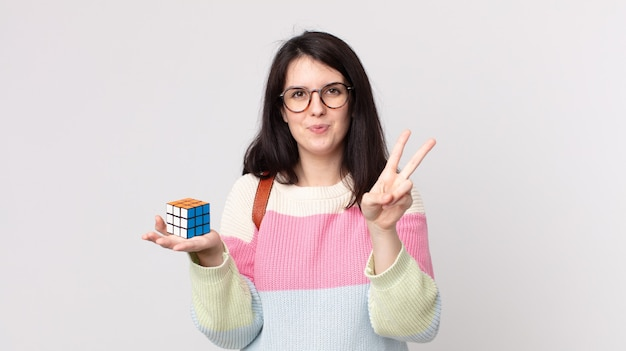 Mooie vrouw die lacht en er vriendelijk uitziet, nummer twee laat zien en een intelligentiespel oplost
