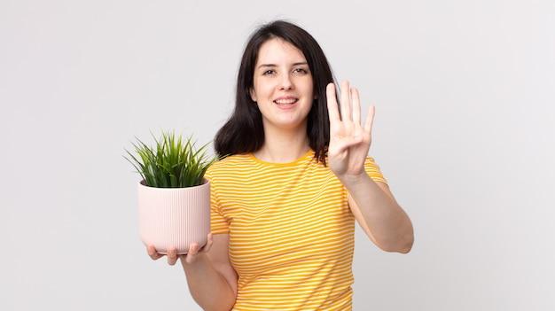 Mooie vrouw die lacht en er vriendelijk uitziet, nummer vier toont en een decoratieve plant vasthoudt
