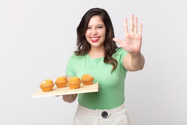 Mooie vrouw die lacht en er vriendelijk uitziet, nummer vijf toont en een dienblad met muffins vasthoudt
