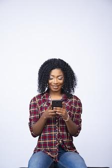 Mooie vrouw die lacht terwijl ze haar telefoon gebruikt, aan het chatten is