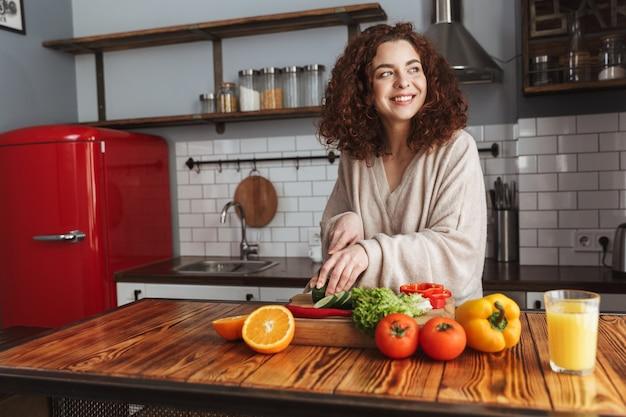 Mooie vrouw die lacht tijdens het koken van salade met verse groenten in het interieur van de keuken thuis