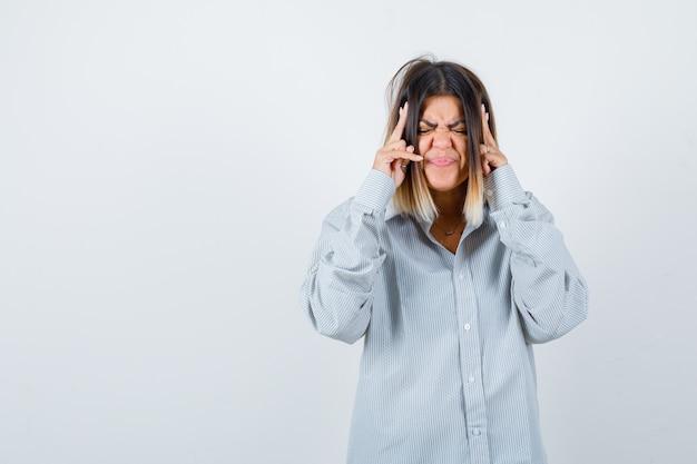 Mooie vrouw die lijdt aan sterke hoofdpijn in shirt en er verdrietig uitziet, vooraanzicht.