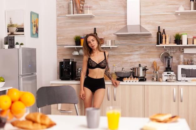 Mooie vrouw die lingerie in huiskeuken draagt tijdens ontbijt. jonge sexy verleidelijke bloeddame met tatoeages die gezond, natuurlijk, zelfgemaakt sinaasappelsap drinken, verfrissende zondagochtend