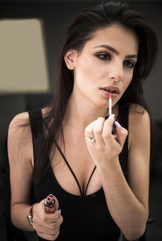 Mooie vrouw die lipgloss toepast