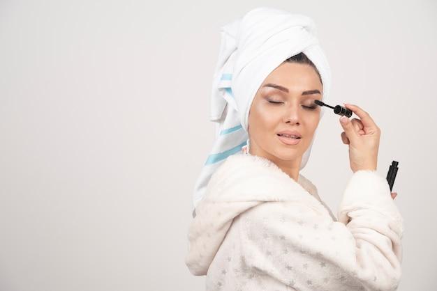 Mooie vrouw die mascara in handdoek op een witte achtergrond gebruikt.