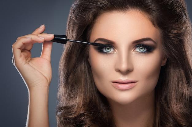 Mooie vrouw die mascara op haar zwepen toepast
