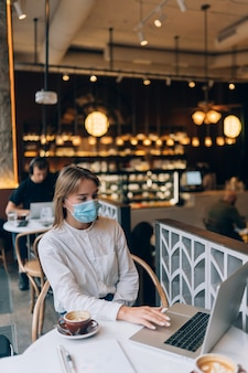 Mooie vrouw die medisch gezichtsmasker draagt dat laptop met behulp van om te werken