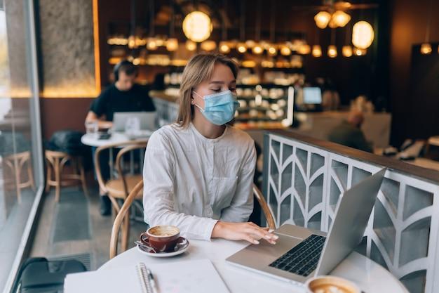 Mooie vrouw die medisch gezichtsmasker draagt die laptop gebruikt om te werken
