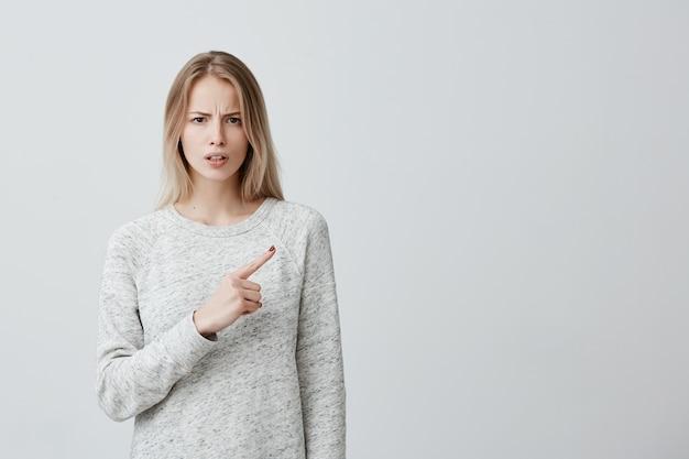 Mooie vrouw die met blond geverfd haar iets met afschuw en ontevredenheid bekijkt die haar wijsvinger richt, die exemplaarruimte toont
