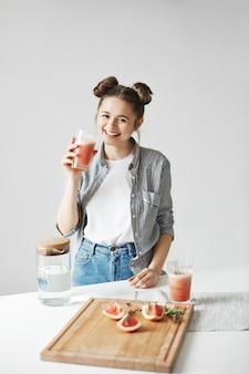 Mooie vrouw die met broodjes het drinken grapefruit detox smoothie over witte muur glimlachen. gezonde voeding