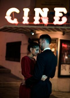 Mooie vrouw die met de jonge mens op straat in avond koestert