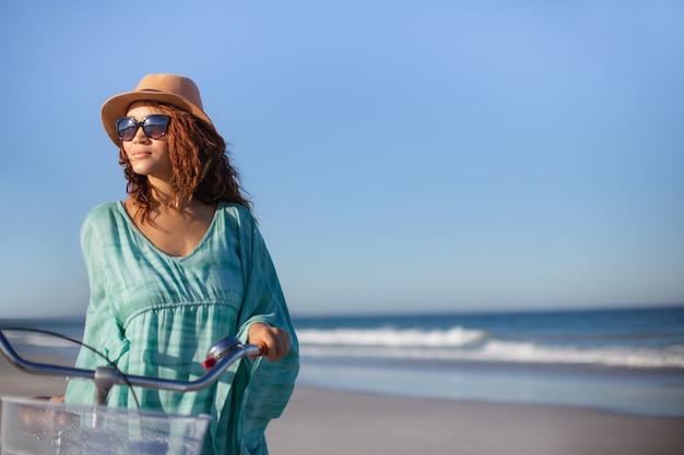 Mooie vrouw die met fiets op strand in de zonneschijn loopt