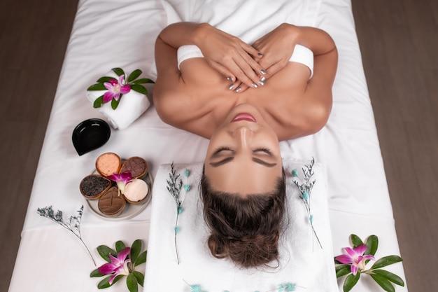 Mooie vrouw die met gelukkige stemming op vakantiedag ligt. wellness lichaamsverzorging en spa aromatheraphy concept.
