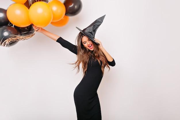 Mooie vrouw die met glanzend haar oranje halloween-ballons houdt