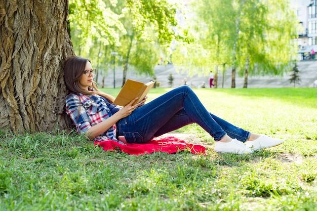 Mooie vrouw die met glazen boek leest