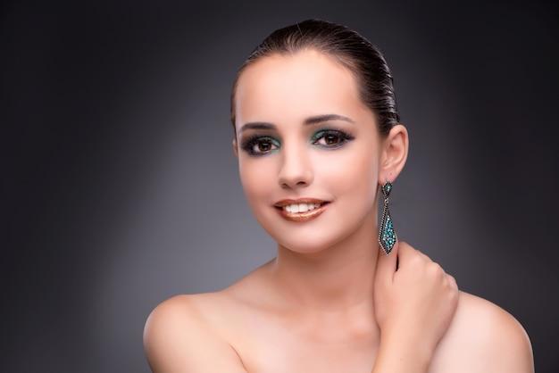 Mooie vrouw die met haar juwelen in manierconcept pronken