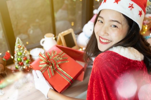 Mooie vrouw die met haar open giftdoos en vrolijke die kerstmistoebehoren glimlachen in ruimte worden verfraaid.