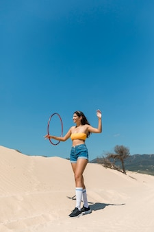 Mooie vrouw die met hulahoepel loopt op zand