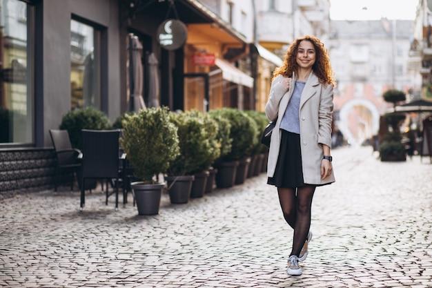 Mooie vrouw die met krullend haar bij een koffiestraat loopt