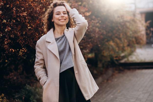 Mooie vrouw die met krullend haar in een de herfstlaag loopt
