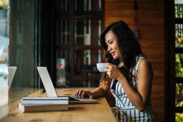 Mooie vrouw die met laptop computer bij koffiewinkelkoffie werkt