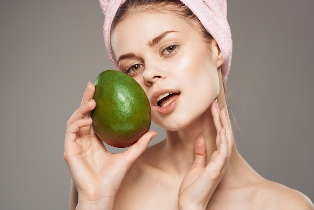 Mooie vrouw die met naakte schouders mango houdt