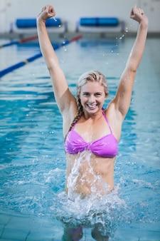 Mooie vrouw die met opgeheven wapens in de pool zegeviert