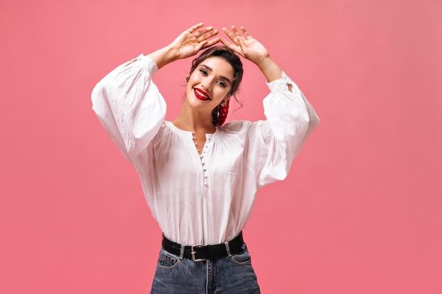 Mooie vrouw die met rode lippen op roze achtergrond glimlacht. donkerharige mooie dame in lichte blouse vormt op geïsoleerde achtergrond.