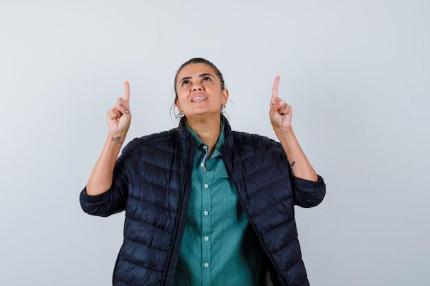 Mooie vrouw die met wijsvingers omhoog wijst in groen shirt, zwarte jas en er vrolijk uitziet. vooraanzicht.