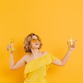 Mooie vrouw die met zonnebril glas limonade houdt