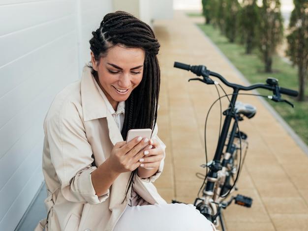 Mooie vrouw die mobiele telefoon doorbladert